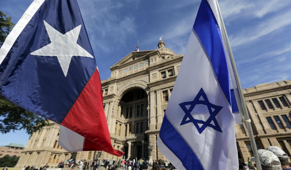 The Texas and Israeli flags are waved by protesters who gathered to disrupt and heckle a group gathered for a Texas Muslim Capitol Day rally, Thursday...