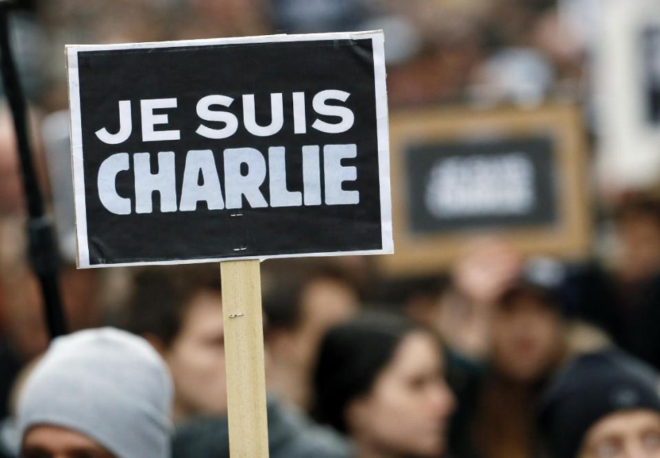 """People hold a poster reading """"Je suis Charlie (I am Charlie)"""" during a rally in Paris on January 11, 2015 in tribute to the 17 victims of a three-day ..."""