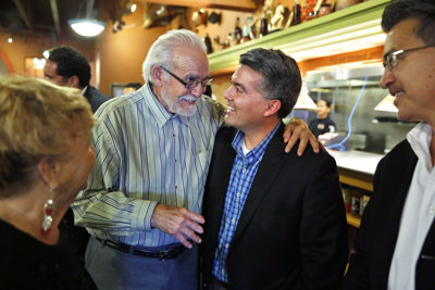 U.S. Rep. Cory Gardner, center right, who is running for the U.S. Senate, talks with supporter Don Trujillo during a meeting and a press conference with state Republican Hispanics, at a Mexican restaurant in Aurora, Colo., Wednesday, Sept. 24, 2014. (AP Photo/Brennan Linsley)