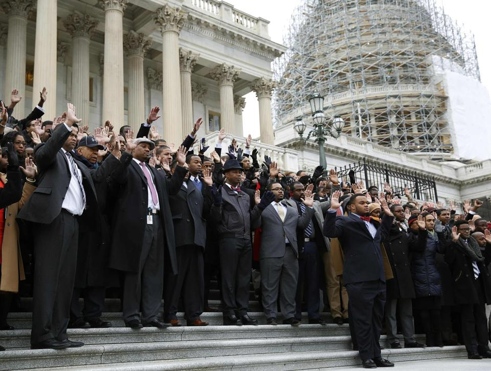 African-American Congressional staffers stage walk out with Hands Up Don't Shoot pose on the steps of the House of Representatives in Washington...