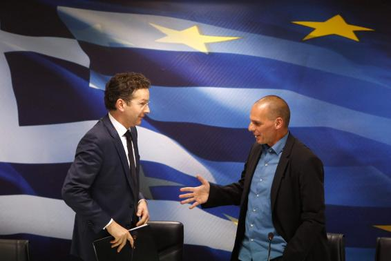 Jeroen Dijsselbloem, (L) head of the euro zone finance ministers' group, and Greek Finance Minister Yanis Varoufakis shake hands after their common press conference at the ministry in Athens January 30, 2015.  REUTERS-Kostas Tsironis
