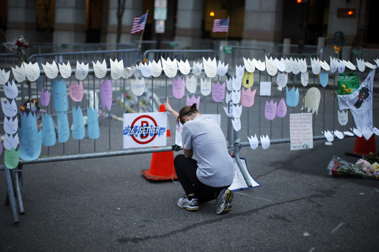 A woman kneels and cries in front of a memorial to the Boston Marathon bombings victims, at the barricades surrounding the scene in Boston, Massachusetts in this April 18, 2013 file photo. (Brian Snyder/REUTERS)