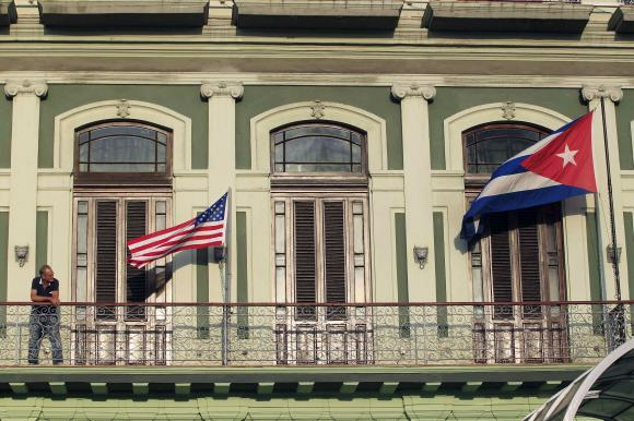 A man stands near the national flags of the U.S. and Cuba (R) on the balcony of a hotel being used by the first U.S. congressional delegation to Cuba since the change of policy announced by U.S. President Barack Obama on December 17, in Havana, January 19, 2015. REUTERS/Stringer